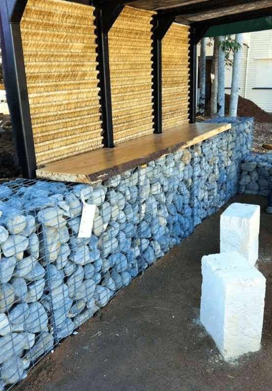 Bar counter is made of wooden table top and gabion mesh